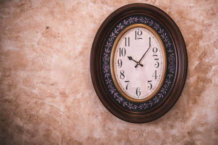 Classic Antique Clock Hanging on Isolated Retro Wall Background, Vintage Ellipse Timer Clock.