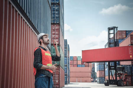 Container Logistics Shipping Management of Transportation Industry, Transport Engineer Managing Control Via Walkie Talkie in Containers Shipyard. Business Cargo Ship Import/Export Factory Logistic. Imagens