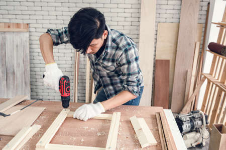 Carpenter Man is Working Timber Woodworking in Carpentry Workshops, Craftsman Using Screwing Equipment to Timber Plank for Wooden Furniture in Workshop. DIY Workmanship, Job Carpenters Concept