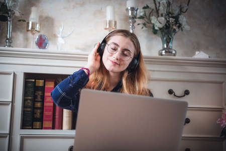 Leisure Activity and Home Relaxing Lifestyle Concept, Attractive Woman Having Enjoyment While Listening Music Songs Via Headphone on Laptop in Living Room. Relaxation Pursuit Entertainment at Home