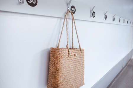 Ecology Living Zero Waste and Sustainable Concept, Straw Natural Material Women Hand Bag Hanging on Hooks in Front of Resting Room. Reusable and Eco Friendly of Women Fashion Bag Accessories