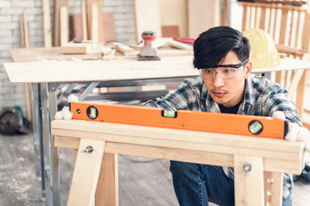 Carpenter Man is Working Timber Woodworking in Carpentry Workshops, Craftsman is Leveling Alignment to Timber Plank for Wooden Furniture in Workshop. DIY Workmanship, Job Carpenters Concept Imagens