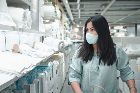 Customer Asian Woman Wearing Face Mask With Shopping Cart in Supermarket Department Store Shop While Choosing and Looking Goods on Shelf During Covid-19 Pandemic. Coronavirus Covid Situation