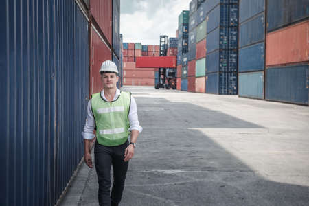 Container Ship Logistics Engineer Worker is Working in Yard Shipping Terminal, Business Cargo Transport and Commercial Dock of Transportation Industry. Engineering Control of Containers Shipment