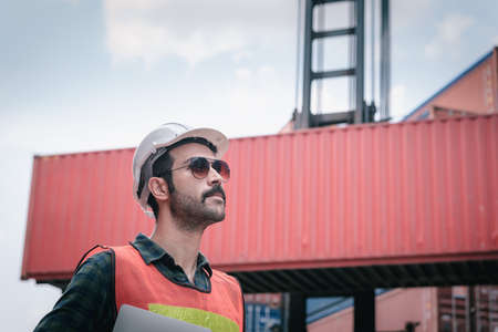 Portrait of Confident Transport Engineer Man in Safety Equipment Standing in Container Ship Yard. Transportation Engineering Management and Container Logistics Industry, Shipping Worker Occupation