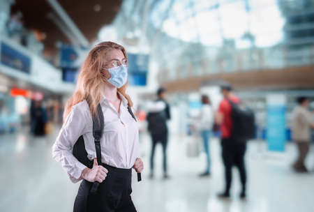 Tourist Woman With Protection Face Mask at The Airport Terminal in Coronavirus Covid-19 Pandemic, Defensive Measure for Travel Restrictions of Tourist During Covid 19 Outbreak. Healthcare/Medical