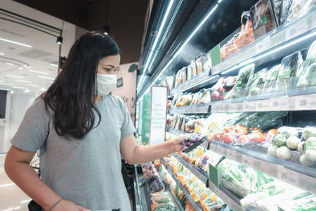 Customer Asian Woman Wearing Face Mask With Shopping Cart in Supermarket Department Store Shop While Choosing and Looking Vegetables on Shelf During Covid-19 Pandemic. Coronavirus Covid Situation