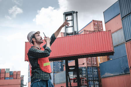 Transport Container Engineer Managing Control Via Walkie Talkie in Containers Shipyard. Container Logistics Shipping Management of Transportation Industry, Business Cargo Ship Import/Export Factory