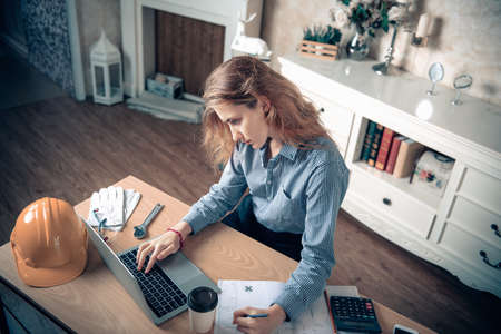 Engineer or Architect Worker Woman is Working at Home Workplace, Portrait of Female Engineer Using CAD on Laptop While Sketch Drawing on Blueprint at Home office. Engineering Occupation Concept Imagens