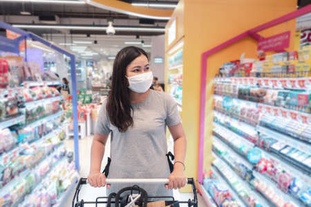 Customer Asian Woman Wearing Face Mask With Shopping Cart in Supermarket Department Store Shop While Choosing and Looking Something on Shelf During Covid-19 Pandemic. Coronavirus Covid Situation