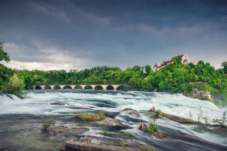 Natural Scenery of Rhine Falls and Swiss Church Culture at Schaffhausen City, Switzerland. Beautiful Nature Waterfront View of Rhine River With Architecture Historical Church Building in Summer.