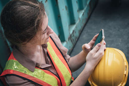 Female Construction Worker Using Mobile Phone While Resting in Workshop Warehouse, Close-Up of Logistics Woman Labor Used Smartphone and Touchscreen in Factory. Technology and Jobs Industry Concept
