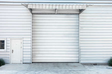Steel Shutter Roller Door of Factory Warehouse Workshop for Materials Storage, Front View of Rolling Metal Doors for Access and Security. Gate Building Structure of Warehouses for Store Imagens