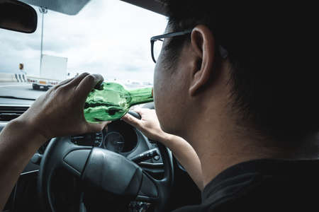 Man Driver Drinking Alcohol and Drunk While Driving a Car, Drunken Man Loose Control and Vitsual Visibility During Drive a Vehicle Car. Illegal Violation and Accident Risk. 版權商用圖片