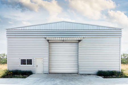 Steel Shutter Roller Door of Factory Warehouse Workshop for Materials Storage, Front View of Rolling Metal Doors for Access and Security. Gate Building Structure of Warehouses for Store 免版税图像