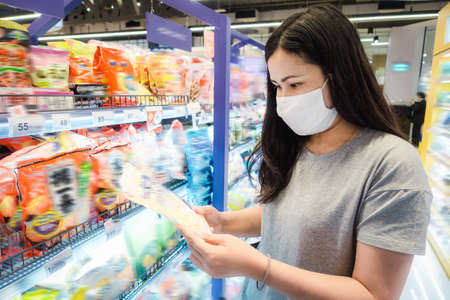 Customer Asian Woman Wearing Face Mask With Shopping Cart in Supermarket Department Store Shop While Choosing and Looking Goods on Shelf During  Pandemic.