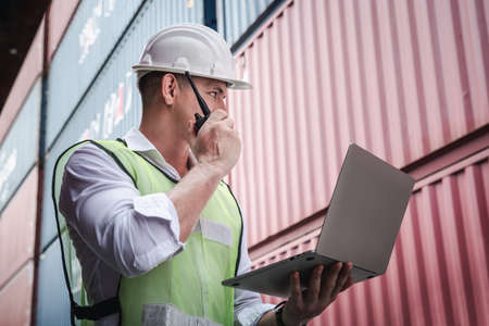 Container Logistics Shipping Management of Transportation Industry, Transport Engineer Managing Control Via Computer Laptop in Containers Shipyard. Business Cargo Ship Import/Export Factory Logistic.
