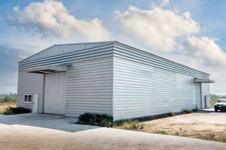 Steel Shutter Roller Door of Factory Warehouse Workshop for Materials Storage, Front View of Rolling Metal Doors for Access and Security. Gate Building Structure of Warehouses for Store 版權商用圖片