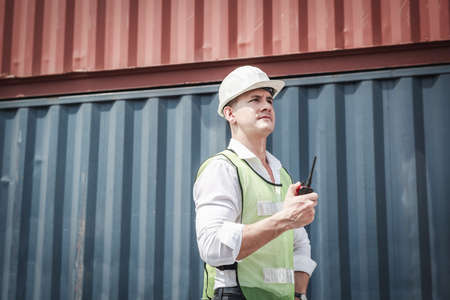 Logistic Container Shipping Engineer in Safety Protective Working at Cargo Shipyard. Transport Engineer Man Inspection Containers Import-Export Freight at Dock Ship. Industrial Transportation and Port