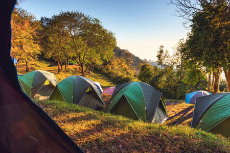 Campground Adventure With Camping Tent of Tourist Backpack, Resting Campfire Picnic at The Highland With Nature Landscape Scenery Background. Holiday Leisure Activity and Summer Vacation Tour