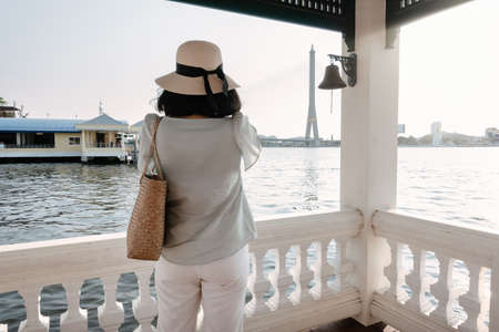 Tourist Woman Having Fun While Sightseeing Bangkok Cityscape beside The River, Rear View of Asian Tourist Woman Relaxing and Enjoy While Photographing Architecture on Her Mobile Phone.