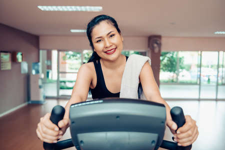 Sport Woman is Cycling Exercise in Fitness Club, Attractive Asian Woman is Training Workout With Bicycle Equipment Machine in Fitness Gym. Healthy Wellness Lifestyle and Exercised Weights Loss Banco de Imagens