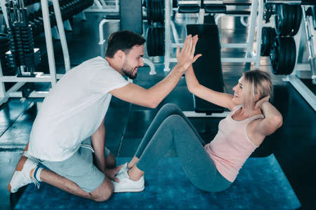 Attractive fitness couple love giving high five together after workout in fitness gym., Portrait of man and woman sporty are working out training together., Couple fitness and healthy concept. Banco de Imagens