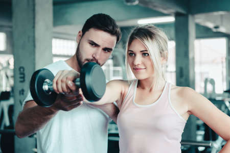 Sporty Woman is Exercising Train While Lifting Dumbbell With Her Trainer in Fitness Room, Sport Woman Having Exercised Workout Training With Male Trainer Together in Fitness Club. Sport Lifestyles