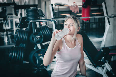 Beautiful Woman is Drinking Water From Bottle After Working Out in Fitness, Portrait of Athletic Woman is Drinking Water After Exercising in Front of Bodybuilder Machine in Gym. Sport Exercise Concept Banco de Imagens
