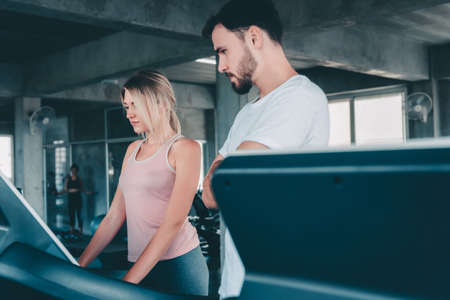 Sporty Woman in Sportswear is Exercising Training on Treadmill Machine With Her Trainer in Fitness Gym, Sport Woman Exercised on Treadmill Running Machines in Fitness Club. Sport Exercises Training