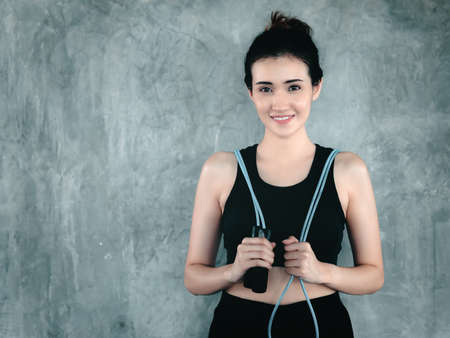 Sport Woman in Sportswear With Holding Skipping Rope in Fitness Gym. Attractive Smiling Sport Asian Girl Exercise With Skipping Rope in Fitness Club. Exercising Lifestyles and Healthy Sport Training Banco de Imagens
