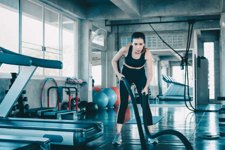 Sporty Woman is Workout Exercising in Fitness Club, Attractive Woman is Effort Exercised With Roping Equipment in Gym. Female Sport Concentrate Exercise in Fitness Gym. Sport Lifestyles and Healthy