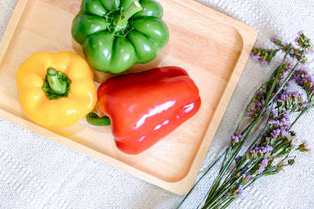 Sweet Pepper Preparation for Cooking. Raw Mix Variety Red, Green, Yellow Sweet Peppers in Wooden Traly on Kitchen Table. Raw Organic Sweet Pepper Ready to Eat for Nutrition Health. Banco de Imagens