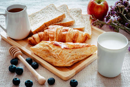 Continental Breakfast With Fresh Baked Croissants, Pie, Sliced Bread and Milk on Kitchen Table, Bakery Homemade for Breakfast. Tasty Meal and Ready to Eat With Bun Bake in The Morning. Breakfast Foods