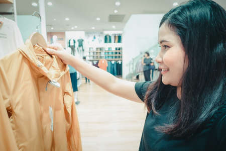 Promotion Sale and Clothes Shopping Concept, Shopaholic Woman is Looking for Choosing Clothes in Shopping Department Store. Attractive Woman Enjoying While Shopping in Mall Shop. Leisure Lifestyles