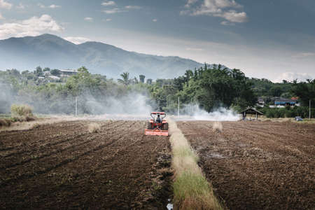 Farm Worker Drove Tractor for Tillage in Agriculture Fields. Farmer Working Soil Plowing Preparation on Tractor Machine for Planting Cultivation. Rural Scenic of Agricultural Farmland During Sunset Banco de Imagens