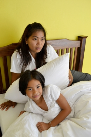 mother and daughter lying in bed photo