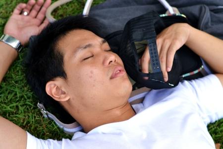 public park: Hombre que duerme en la hierba en el parque p�blico Foto de archivo