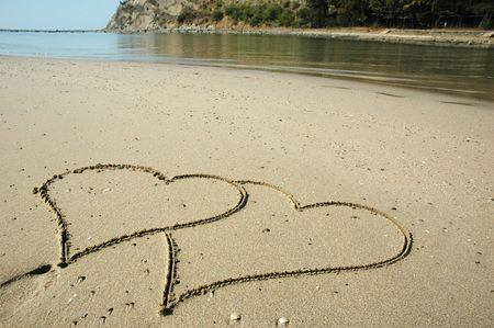 Two hearts drawn on a wet sandy beach Stock Photo