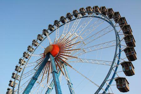 Ferris wheel against bright blue sky on amusement park Stock Photo