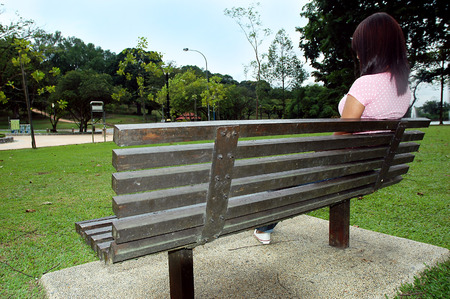 Girl sitting on a bench in a green park Stock Photo - 1631384