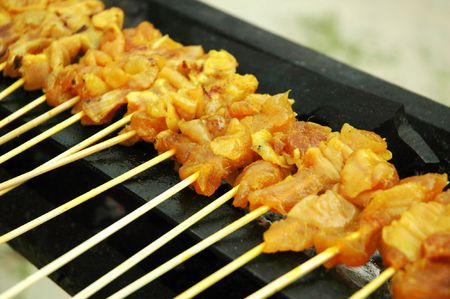 Traditional Malay and Indonesian delicacy of sliced chicken meat on bamboo skewers grilled with charcoal fire photo