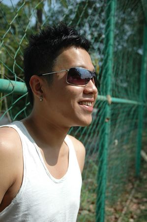Cool young Asian Chinese man wearing sun glasses smiling in a perspective shot Stock Photo