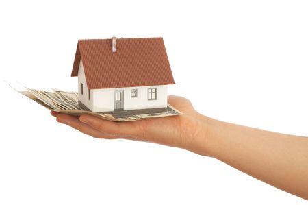 hand holding mini house and Us dollars photo