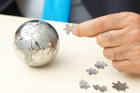 globe puzzle: businessman with globe puzzle