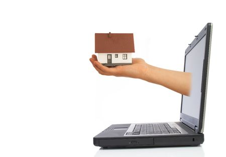 hand giving a mini house from laptop screen with space for messages photo