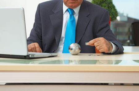 businessman with laptop and mini puzzle globe photo