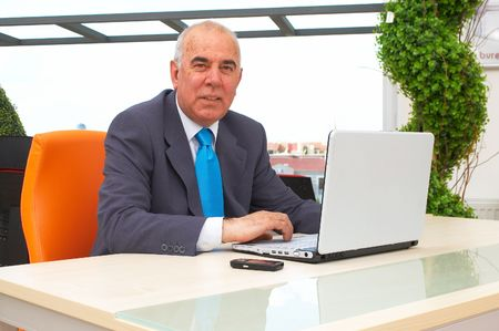 teleworking: senior businessman with laptop at the office