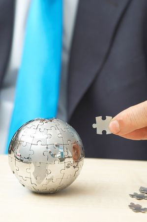 businessman with a mini puzzle globe, trying to solve Stock Photo - 1364781
