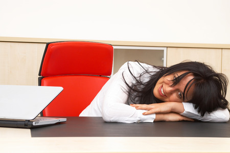 co worker: young businesswoman at the business office with a smile